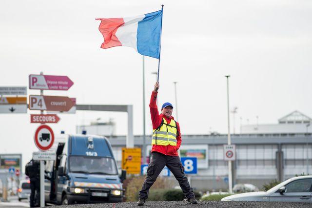 Un manifestant brandit un drapeau français près de l'aéroport de Nantes lors d'une manifestation de Gilets jaunes, à Bouguenais le 8 décembre 2018