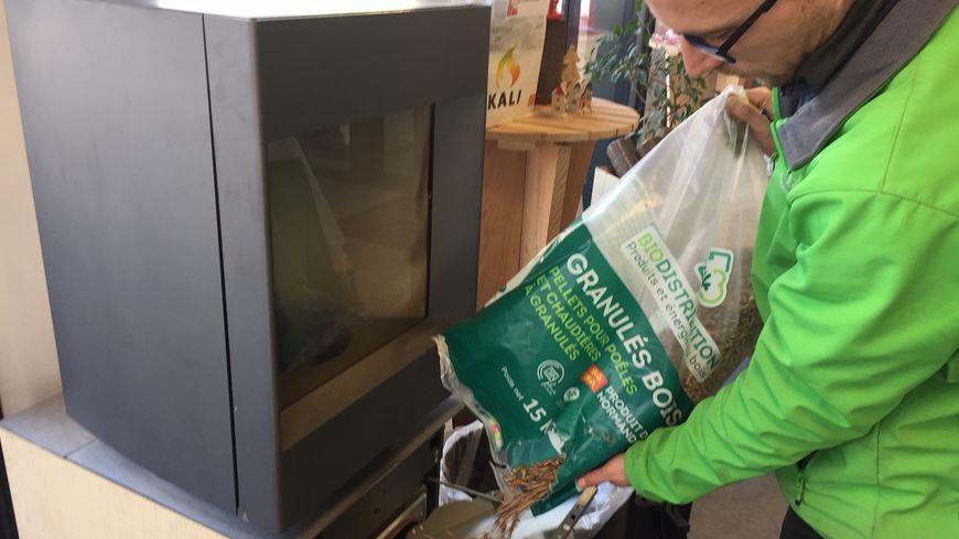 Martin, vendeur chez Biocombustibles, à Soliers au sud de Caen, est en train de remplir un poêle à granulés.