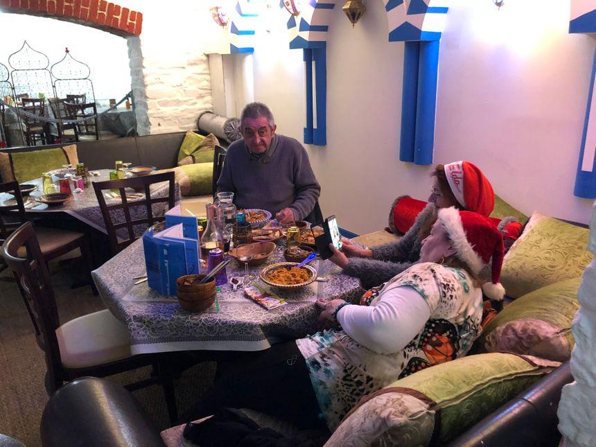 Marc et ses deux amies en plein repas et coiffés du bonnet de Noël