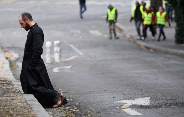 Scène inattendue samedi 8 décembre 2018 sur les Champs-Elysées : un prêtre agenouillé sur le trottoir