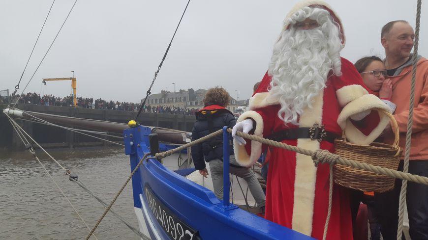 Le père Noël à l'avant de son voilier, la Croix du sud.