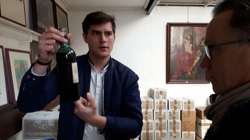 Maxime Guillot, organisateur de la vente,  présente le niveau de vin dans la bouteille à un acheteur intéressé par le lot.