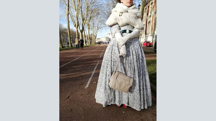 evant le château de Versailles, la jeune couturière pose dans la tenue qui n'a pas plu aux gardiens.