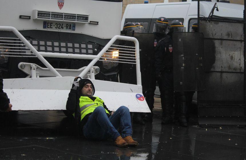 Un manifestant s'assied devant le barrage des forces de l'ordre place Pey-Berland.