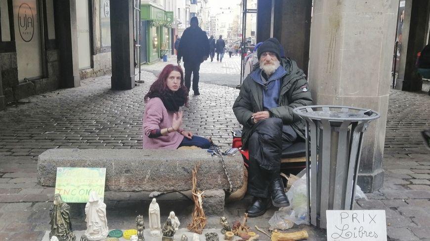 Jean-Philippe est accompagnée d'une de ses amies. Il vend ses créations aux passants.