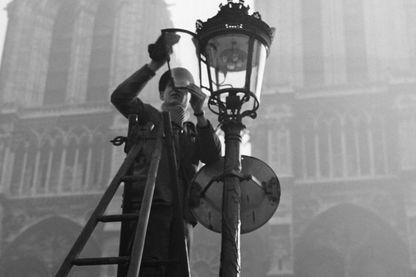 Employé municipal remplaçant une ampoule à Paris
