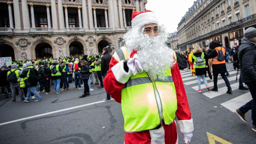 """Un """"gilet jaune"""" déguisé en Père Noël, place de l'Opéra le 15 décembre à Paris."""