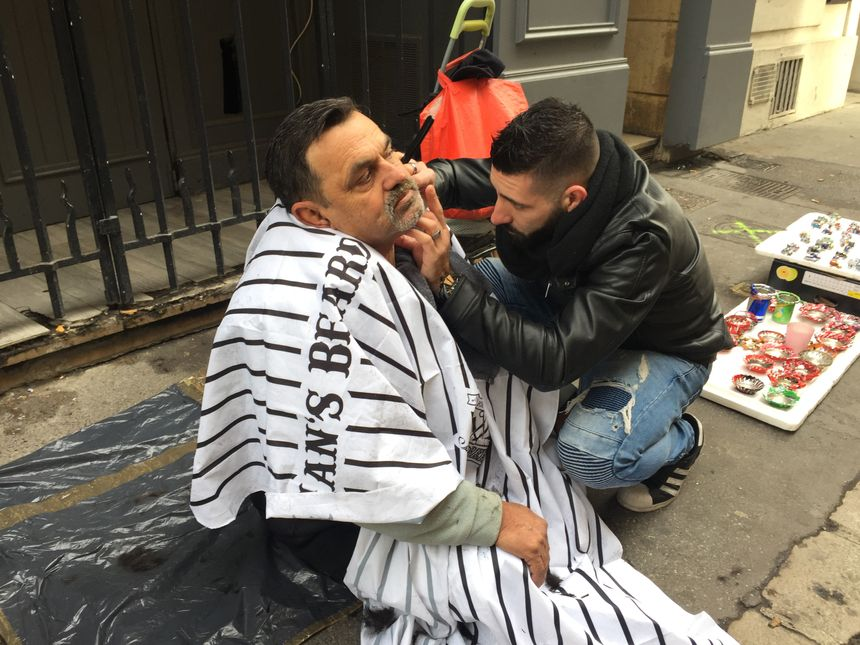 Comme chez le coiffeur, Kévin taille la barbe des sans-abris au milieu de la rue.