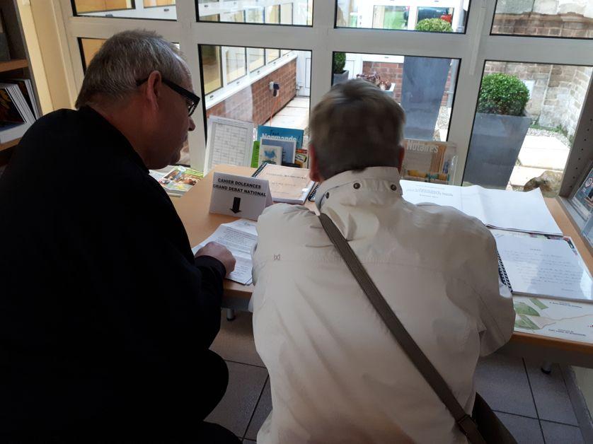 Véronique et Michel écrivent dans le cahier de doléance qui sera remis au président de la République