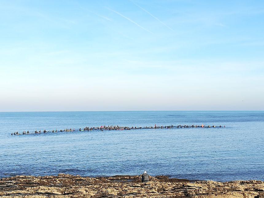 Dans l'océan les surfeurs forment une chaîne humaine sous les applaudissements des badauds