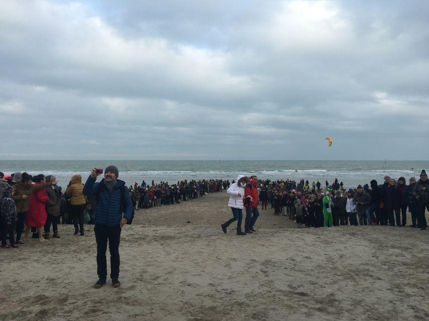 Avant le décompte des douze coups de midi, les spectateurs forment une haie d'honneur devant le millier de givrés qui se jettera à l'eau