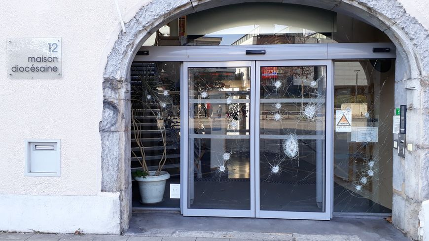 La porte vitrée de la maison diocésaine de Grenoble, constellée d'une vingtaine impacts, occasionnés, peut-être par une barre de fer
