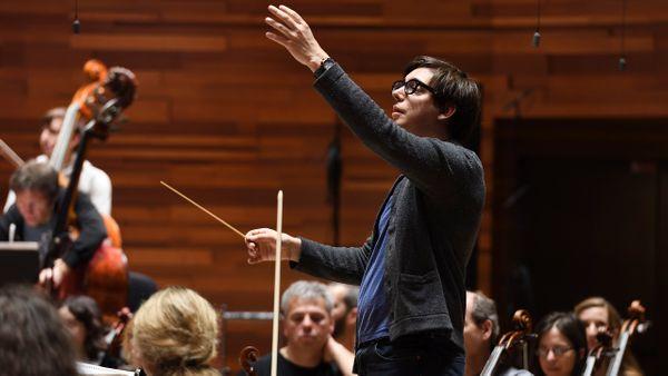 Adrien Perruchon, jeune et déjà fameux chef d'orchestre, dirige la création de Dianoura, musique d'Etienne Perruchon. En répétition avec l'Orchestre Philharmonique de Radio France