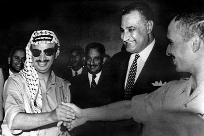 Poignée de mains du leader de l'Olp, Yasser Arafat (gauche) et le Roi Hussein de Jordanie (droite) sous le regard du président égyptien Nasser, 27/09/1970