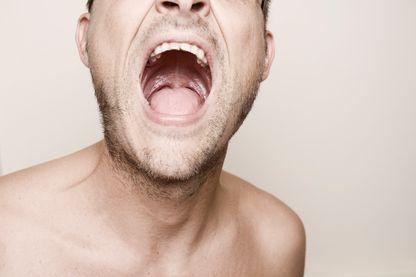 Portrait d'un homme à la bouche grande ouverte.