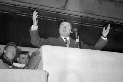 """Pierre Poujade, fondateur de l'UDCA (Union de Défense des Commerçants et Artisans) harangue quelque 80.000 artisans venus de province écouter la parole """"anti-fiscale"""" de leur président, le 24 janvier 1955 à la Porte de Versailles à Paris."""