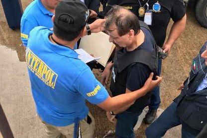 Cesare Battisti escorté par des policiers d'Interpol avant d'embarquer dans un avion affrété par le gouvernement italien à Santa Cruz de la Sierra, en Bolivie, le 13 janvier 2019.