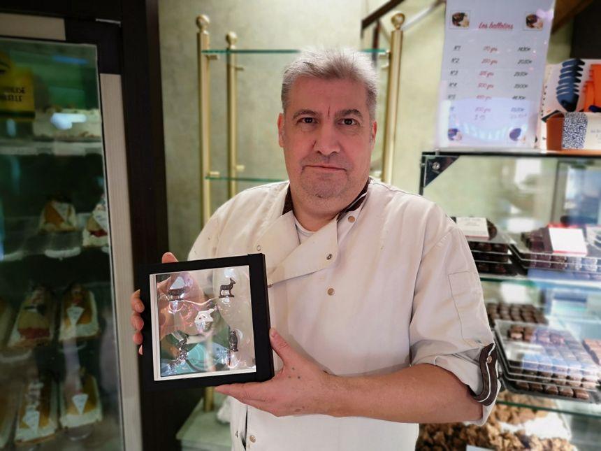 Jean-Marc Joly dans sa boutique, avec un coffret contenant les cinq fèves