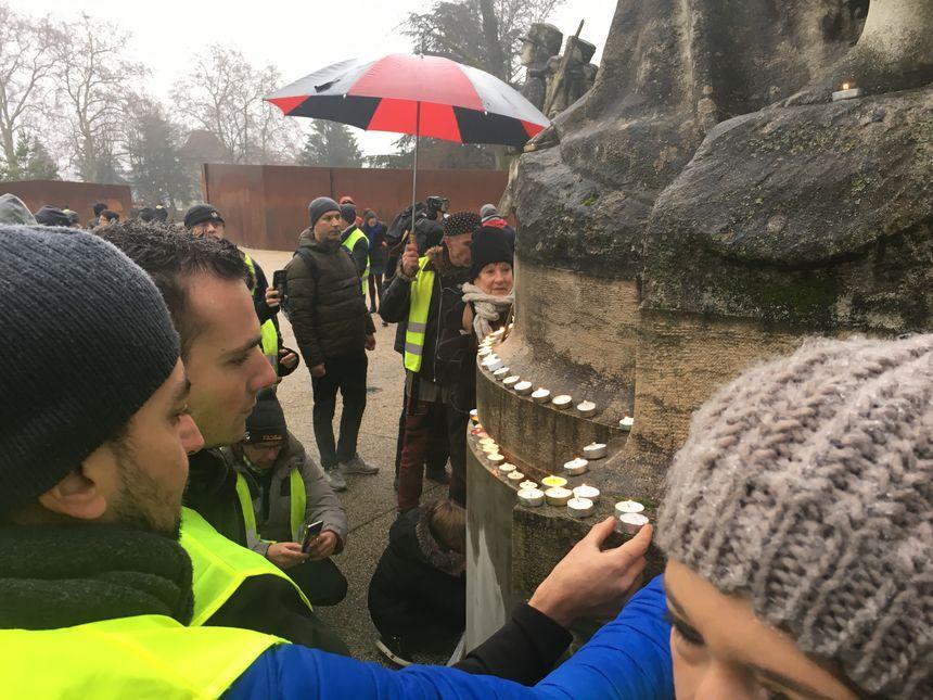 Des gilets jaunes allument des bougies, aux glacis, en hommage aux manifestants morts depuis le début du mouvement dans toute la France