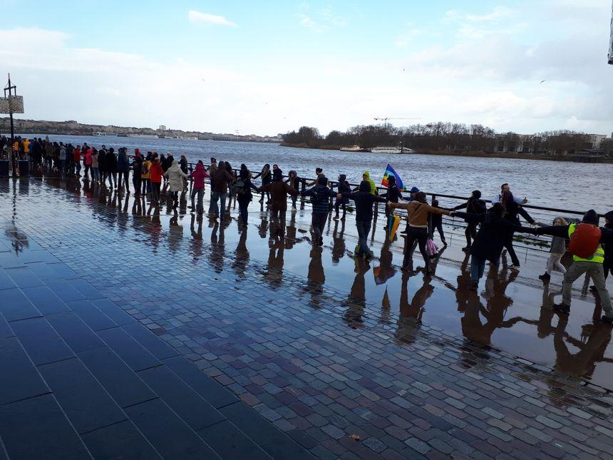 Une chaîne humaine - sous la pluie - devant le miroir d'eau