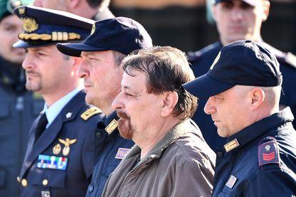 Cesare Battisti est escorté par des policiers à la sortie de son avion à l'aéroport de Ciampino à Rome, la fin de 37 ans de cavale (14 janvier 2019)