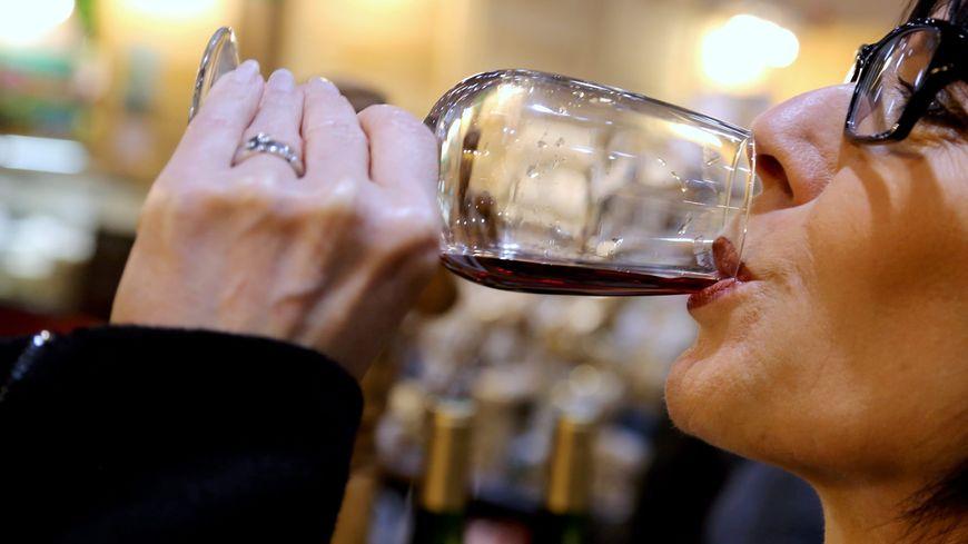Une femme boit un verre de vin ( photo d'illustration)