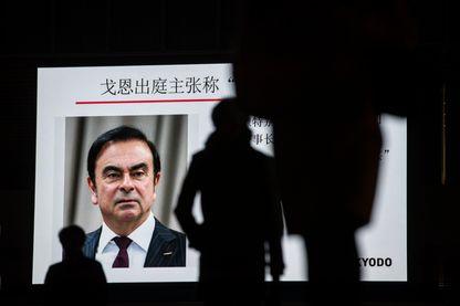 Des piétons passent devant un écran de télévision montrant le portrait de Carlos Ghosn, patron de l'alliance Renault-Nissan, à Tokyo, le 8 janvier 2019.