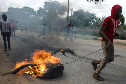 Un manifestant sur la route entre le township d'Epworth et la capitale Harare au Zimbabwe, le 14 janvier 2019