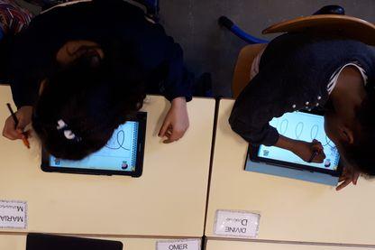 Deux élèves de grande section s'entraînent sur la tablette Kaligo
