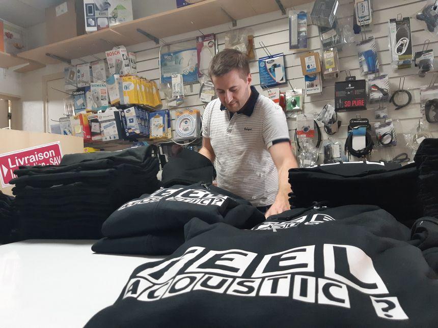Jérémy Pauly, l'un des membres de Trois cafés gourmands, plie des tee-shirts dans le magasin des parents de Sébastien Gourseyrol (autre membre) à Pompadour en Corrèze