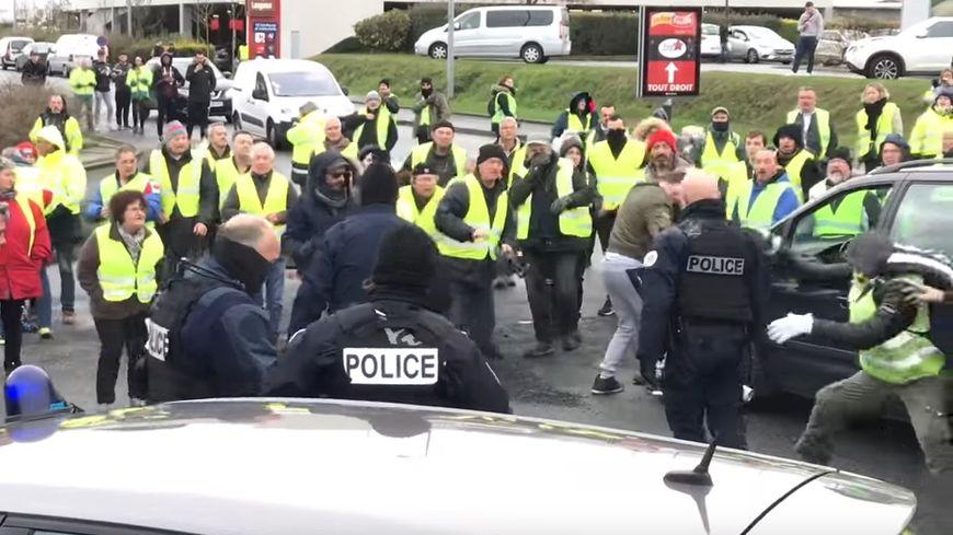 A droite, on distingue un manifestant sur le point de subtiliser la bombe lacrymogène d'un policier
