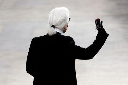 Karl Lagerfeld salue à la fin d'un défilé Chanel au Grand Palais à Paris le 1er octobre 2013.