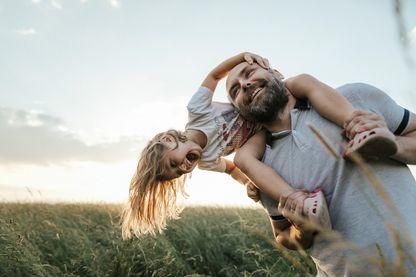 Un homme et une gamine jouant dehors (image d'illustration)