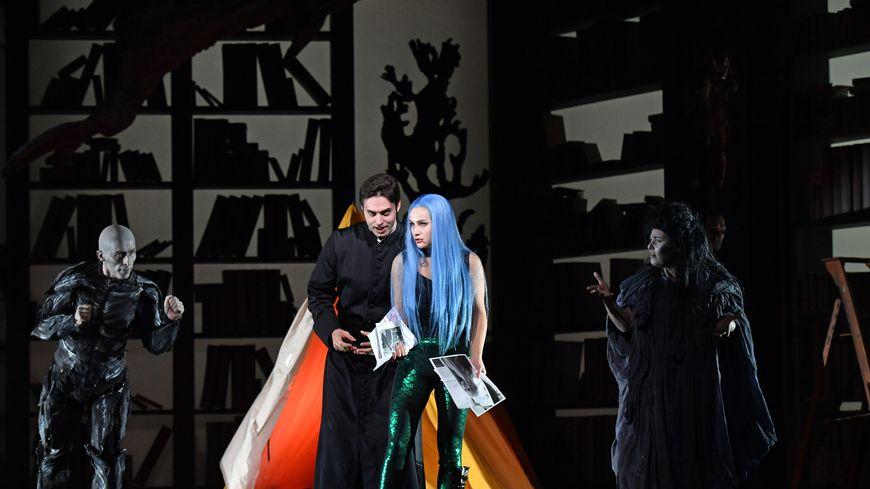 Aux deux extrémités, dans l'ombre, les chansigneurs interprètent le texte mais aussi la musique de la scène jouée par les deux chanteurs.