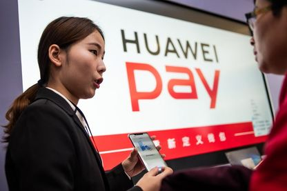 A hostess speaks about the new Huawei smarthone pay service during a press conference and launch of new 5G Huawei products at the Huawei Beijing Executive Briefing Centre in Beijing on January 24, 2019.