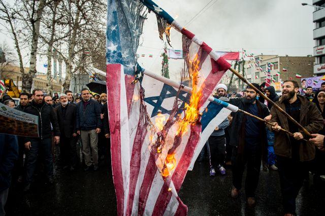 Des Iraniens brûlent des drapeaux américains et israëliens lors des célébrations du 40e anniversaire de la Révolution, le 11 février, à Téhéran