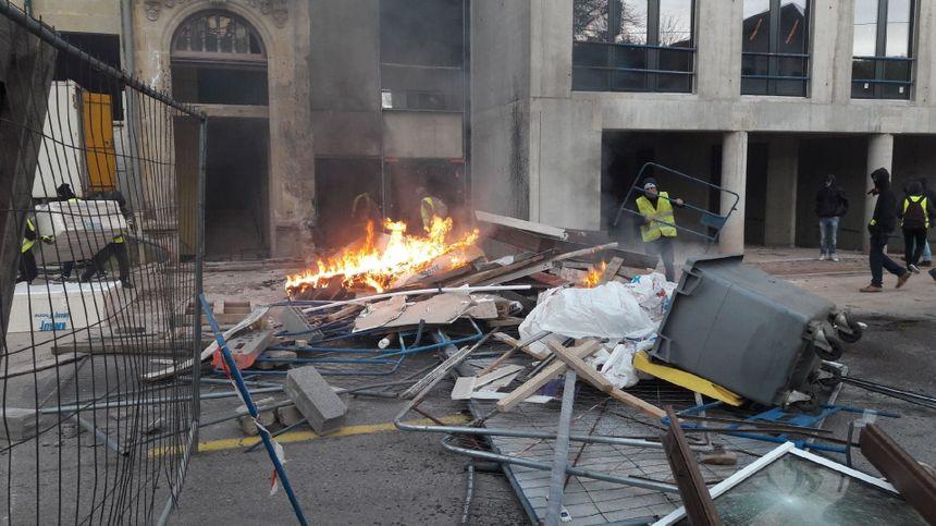 """Barricades des """"gilets jaunes"""" avec des poubelles et matériaux de chantier."""
