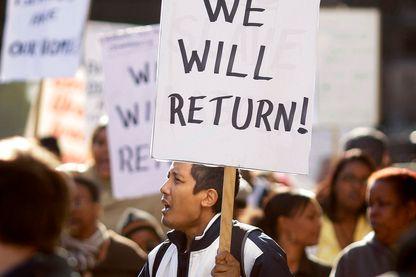 """Un manifestant, natif des îles Chagos, en octobre 2008 lors d'un rassemblement devant le Parlement au Royaume-Uni, avec une pancarte """"Nous y retournerons""""."""