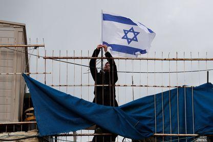 Un colon israélien plante un drapeau sur le toit de la maison de la famille palestinienne Abu Assab, expulsée sur décision de justice, à Jérusalem Est, le 17 février 2019