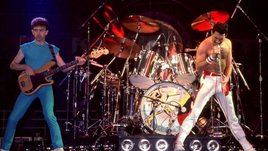 ETROIT, MI - AUGUST 6: Bass guitarist John Deacon, drummer Roger Taylor and British singer-songwriter, record producer and lead vocalist Freddie Mercury (1946-1991) of Queen perform on stage during the Hot Space Tour on August 6, 1982 at the Joe Loui