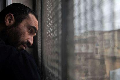 Un homme syrien souffrant de troubles mentaux jette un œil devant une fenêtre dans la ville d'Aldana, dans le nord du pays, près de la deuxième ville d'Alep, en Syrie, le 14 février 2019