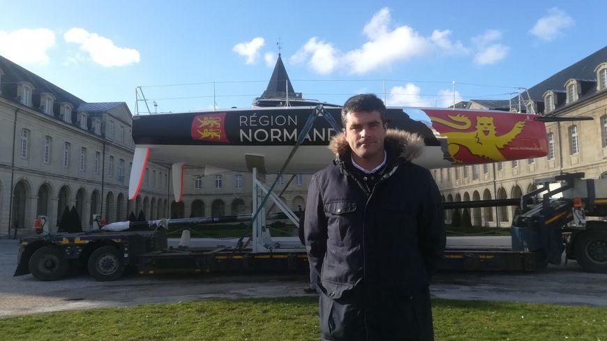 le skipper Alexis Loison pose devant le voilier de la région Normandie devant l'Abbaye aux Dames à Caen