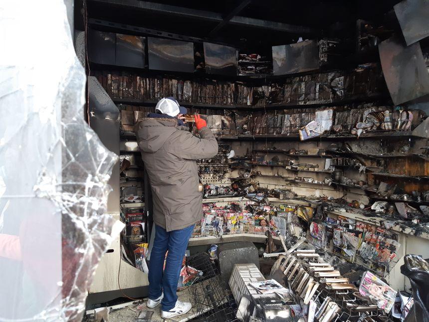 Un kiosquier des Champs-Elysées constate les dégâts et prend des photos pour déclarer le sinistre auprès de son assurance.