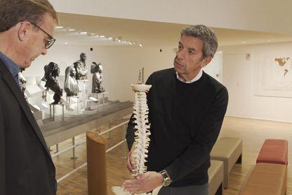 Michel Cymès explique son mal à un patient à l'aide d'une maquette de colonne vertebrale.