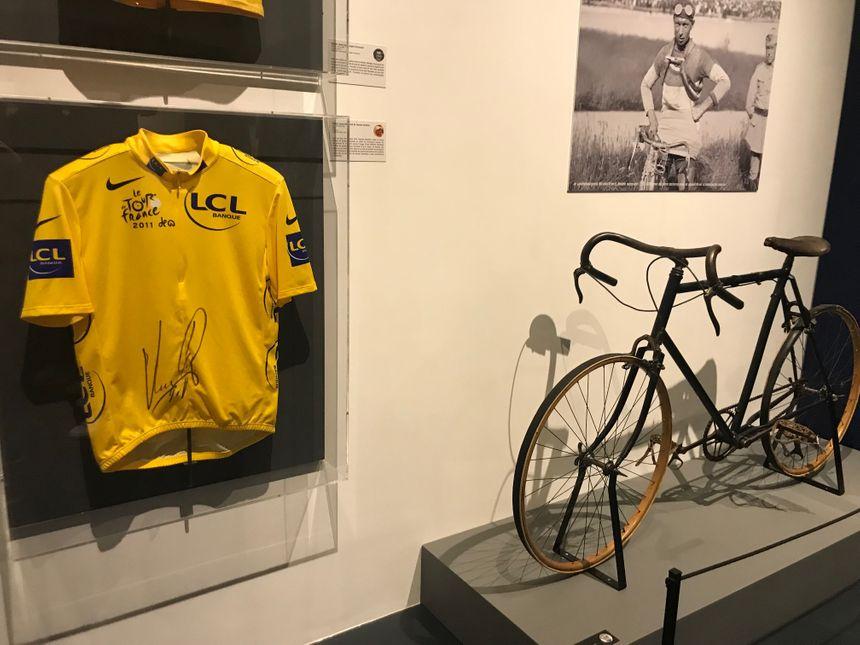 Le maillot jaune porté et signé par Thomas Voeckler près d'un vélo de la fin des années 20