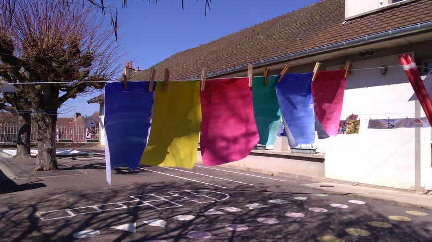 """Des dessins, une corde à linge : l'installation la """"Grande lessive"""" a fière allure dans la cour de la maternelle de Felletin."""