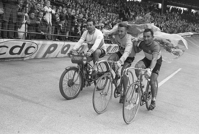 Jacques Anquetil (au centre) alors qu'il venait de remporter le Bordeaux-Paris 1965. Il est soutenu à sa gauche par le cycliste Jean Stablinski.