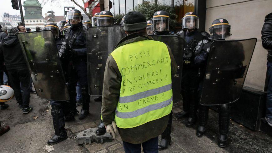 """Des policiers empêchent un """"gilet jaune"""" de passer, lors de l'acte 11 du mouvement des gilets jaunes à Paris, le 26 janvier dernier."""