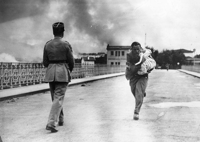A la frontière espagnole, le 16 octobre 1936, un bébé confié par une Républicaine aux bras du reporter Raymond Vanker lors de la prise d'Irun.