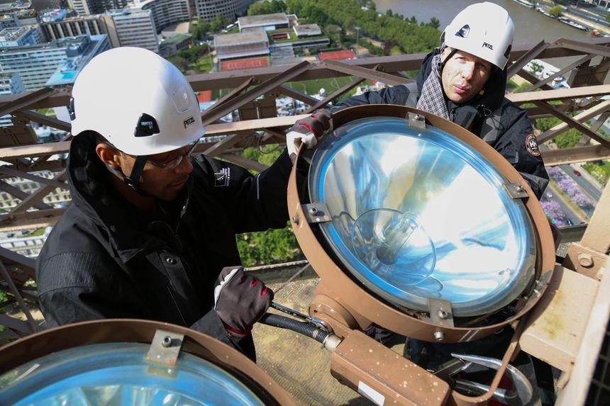 Des électriciens alpinistes changent les ampoules.
